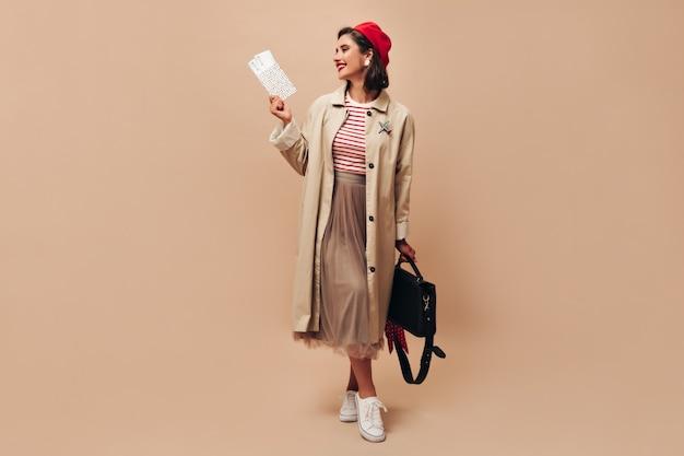 Dame in rode baret en stijlvolle loopgraaf houdt handtas en kaartjes. mooie vrouw in lange rok en witte sneakers poseren op geïsoleerde achtergrond.