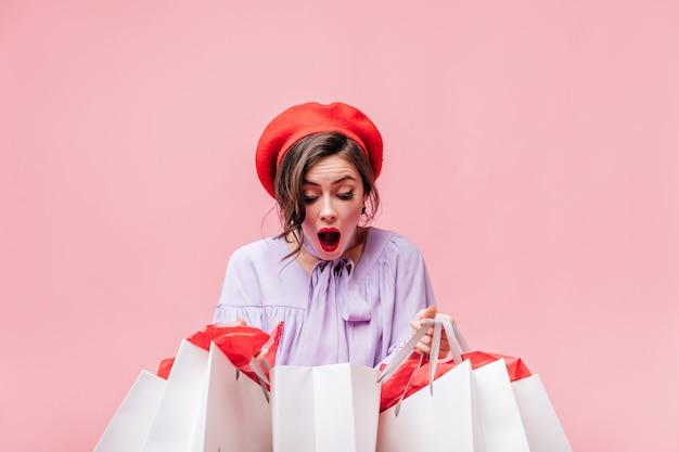 Dame in rode baret kijkt met verbazing naar witte papieren zakken na het winkelen.