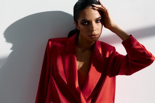 Dame in rode jas en zwarte broek houdt hand in de buurt van gezicht bijgesneden weergave close-up
