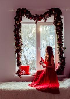 Dame in rode jurk zit op de widnowsill versierd met kerstslinger