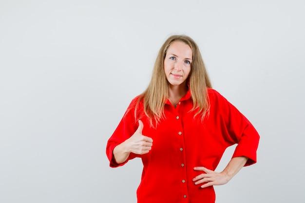 Dame in rood overhemd duim opdagen en er zelfverzekerd uitzien,