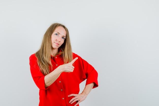 Dame in rood shirt wijst naar de rechterbovenhoek en ziet er zelfverzekerd uit,