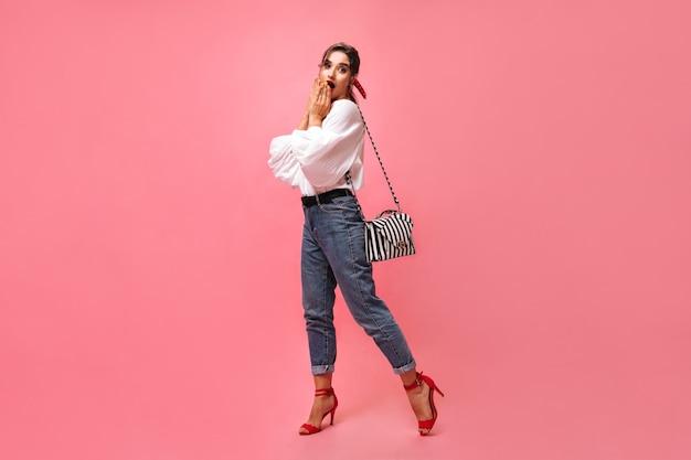 Dame in spijkerbroek en witte blouse kijkt verbaasd op roze achtergrond. geschokt stijlvolle jonge vrouw in schattige rode schoenen kijkt naar camera met handtas.