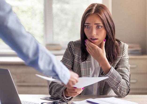 Dame in stijlvolle formele kleding is geschokt als ze een document neemt.