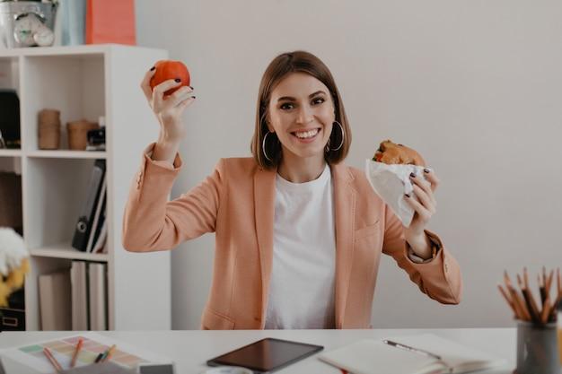 Dame in stijlvolle lichte outfit pronkt met haar lunch bestaande uit appel en hamburger op de werkplek.