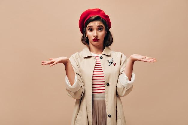 Dame in stijlvolle outfit kijkt met misverstand in de camera. jonge vrouw in rode baret en beige modieuze vacht poseren op geïsoleerde achtergrond.