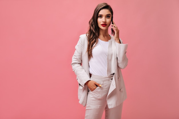 Dame in wit pak onderzoekt de camera en praat over de telefoon. modern meisje in licht t-shirt en crème jasje vormt op geïsoleerde achtergrond.
