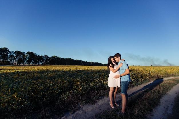 Dame in witte jurk knuffelt haar man ergens in het veld