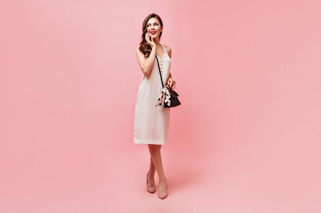 Dame in witte zomerjurk glimlacht zoet en houdt handtas op roze achtergrond.
