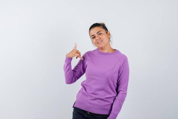 Dame in wollen blouse die een rotsgebaar toont en er zelfverzekerd uitziet