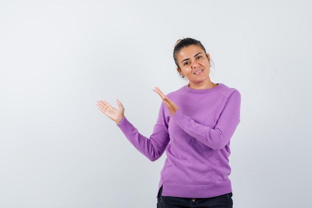 Dame in wollen blouse die een verwelkomend gebaar toont en er zacht uitziet Gratis Foto