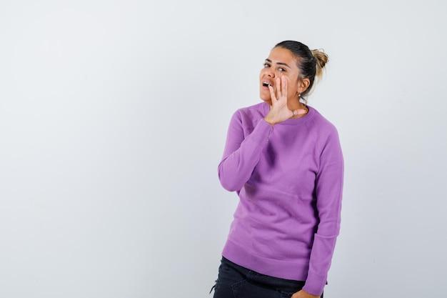 Dame in wollen blouse die geheim achter hand vertelt en nieuwsgierig kijkt