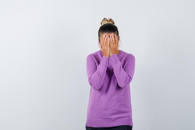 Dame in wollen blouse die gezicht bedekt met handen en er depressief uitziet