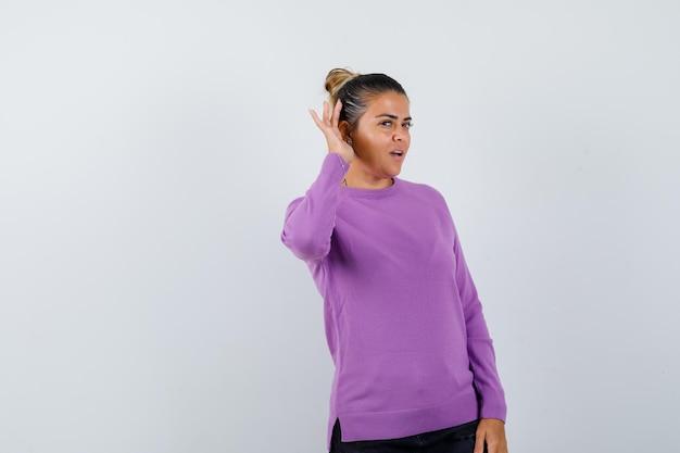 Dame in wollen blouse die hand achter het oor houdt en nieuwsgierig kijkt