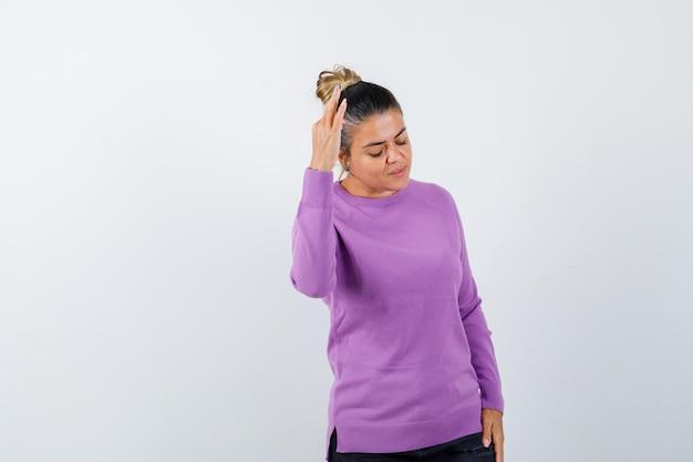 Dame in wollen blouse die hand opsteekt terwijl ze naar beneden kijkt en peinzend kijkt