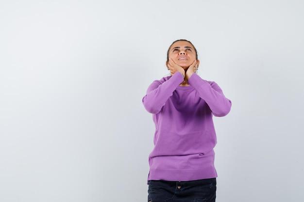 Dame in wollen blouse die het gezicht op haar handen dempt en er prachtig uitziet