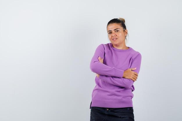 Dame in wollen blouse die met gekruiste armen staat en er zelfverzekerd uitziet