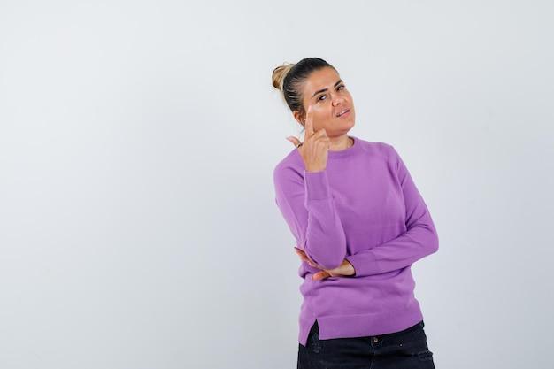 Dame in wollen blouse die naar boven wijst en er zelfverzekerd uitziet