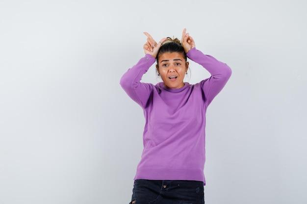 Dame in wollen blouse die vingers boven het hoofd houdt als stierenhoorns en er grappig uitziet