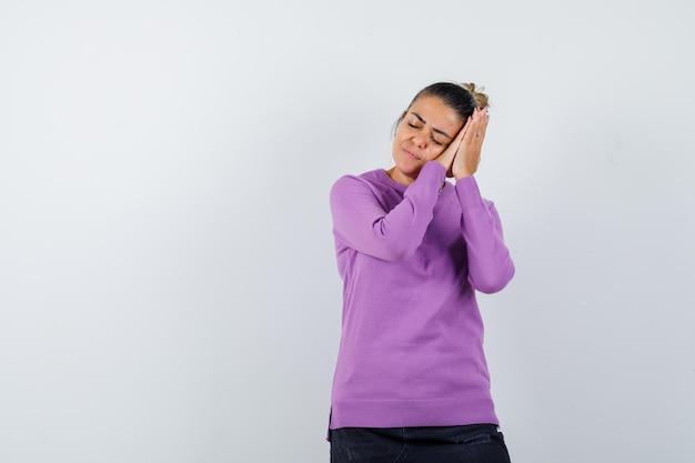 Dame in wollen blouse leunend op handpalmen als kussen en er vredig uitziend