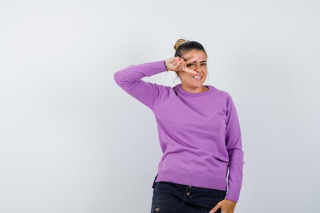 Dame in wollen blouse met v-teken op het oog en ziet er vrolijk uit