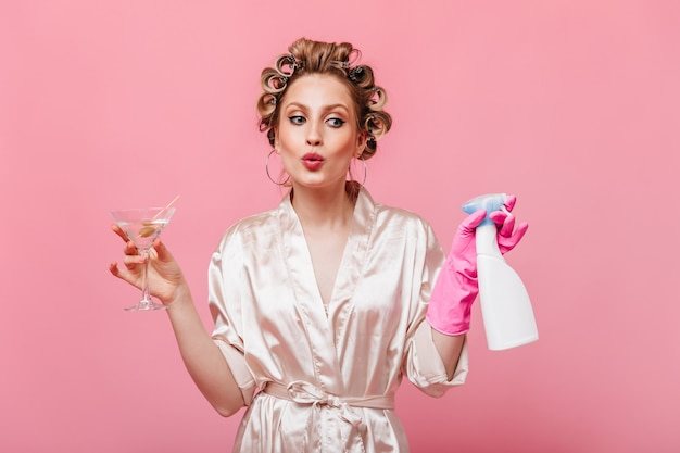 Dame in zijden gewaad fluit, houdt afwasmiddel en martiniglas op roze muur