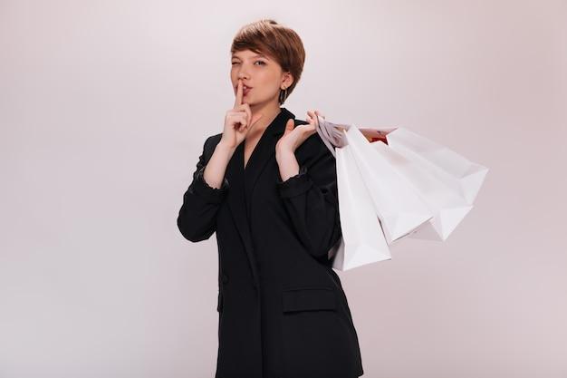Dame in zwart pak vragen om geheim te houden en boodschappentassen, portret van jonge kortharige vrouw in donkere jas poseren op geïsoleerde achtergrond