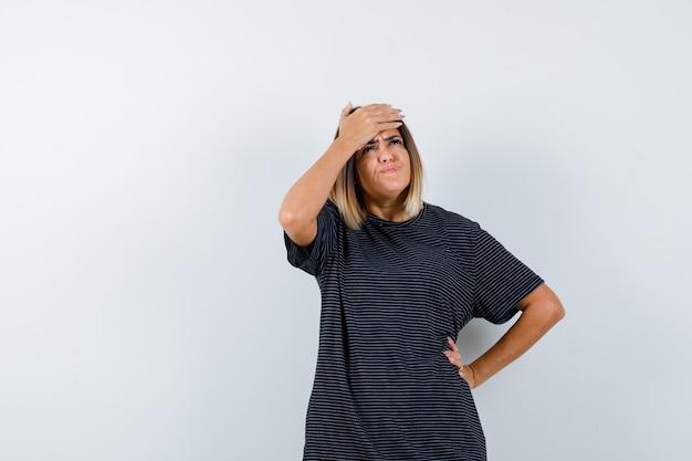 Dame in zwart t-shirt die hand op voorhoofd houdt en hulpeloos, vooraanzicht kijkt.