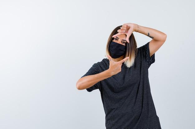 Dame in zwarte jurk, medisch masker frame gebaar maken en op zoek vrolijk, vooraanzicht.