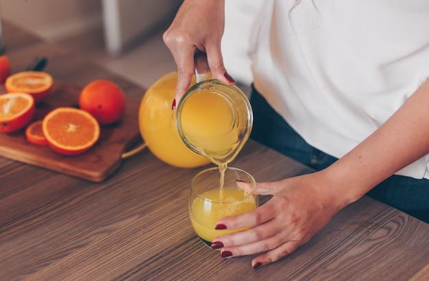 Dame jus d'orange gieten in de keuken