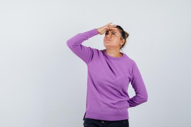 Dame kijkt omhoog met de hand boven het hoofd in wollen blouse en kijkt peinzend