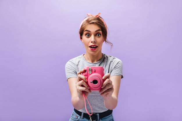 Dame kijkt verbaasd en neemt foto's op roze camera. modieuze jonge vrouw in grijs t-shirt met rode heldere lippen poseren.