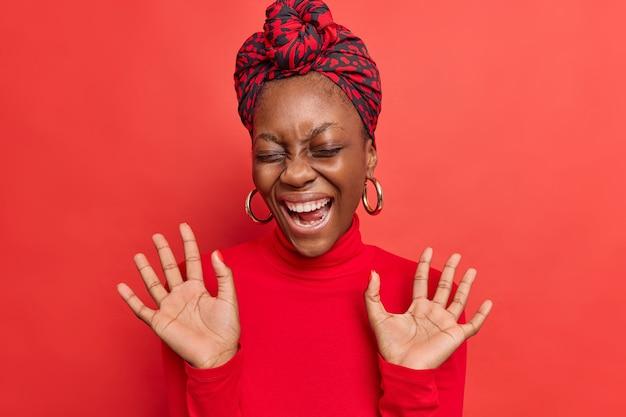 Dame lacht om grappige grap houdt handpalmen omhoog giechelt positief toont witte tanden gekleed in coltrui geïsoleerd op rood