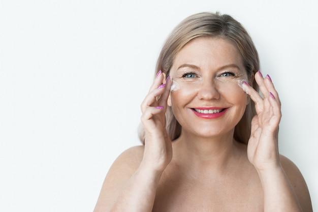 Dame maakt reclame voor iets terwijl ze crème op haar gezicht aanbrengt