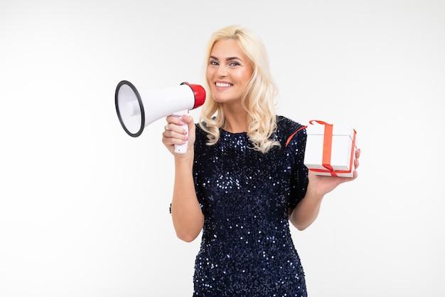Dame met blond haar in een jurk kondigt in een luidspreker over een loting met een geschenkdoos op een witte studio achtergrond