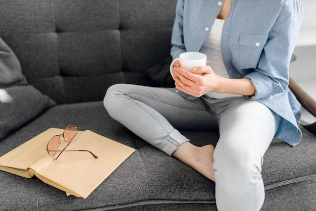 Dame met boek en kopje koffie op zwarte bank