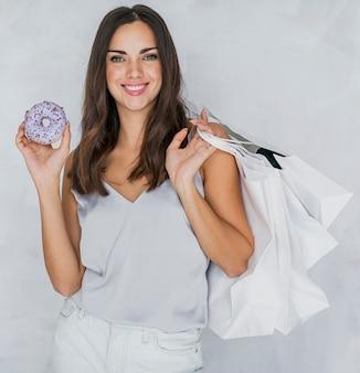 Dame met een doughnut en winkelnetten die aan de camera glimlachen