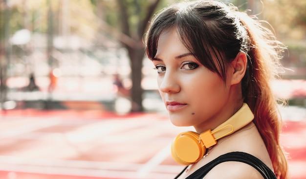 Dame met een serieuze blik gebruikt een gele koptelefoon