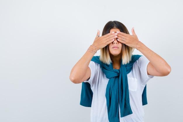Dame met gebonden trui die de handen op de ogen houdt in een wit t-shirt en er bang uitziet. vooraanzicht.