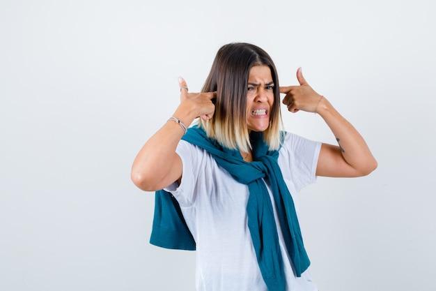 Dame met gebonden trui in wit t-shirt die oren stopt met vingers en er geïrriteerd uitziet, vooraanzicht.