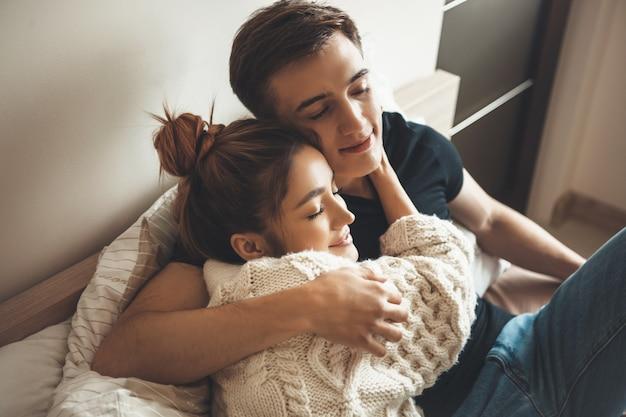 Dame met gebreide trui omhelst haar minnaar in bed met gesloten ogen