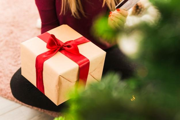 Dame met geschenkdoos en plastic kaart op tapijt