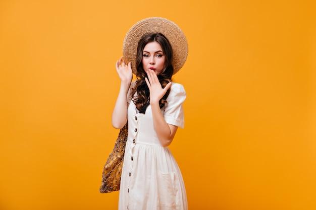 Dame met groene ogen bedekt haar mond met haar hand. vrouw in strooien hoed en witte sundress houdt boodschappentas op oranje achtergrond.