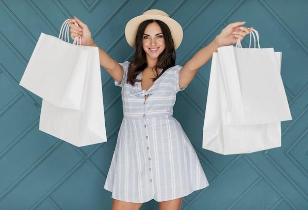 Dame met jurk die de winkelnetten oppakt