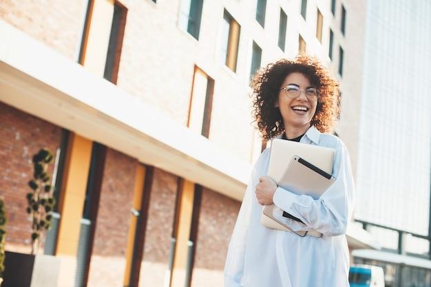 Dame met krullend haar poseert buiten met een paar moderne gadgets tijdens het lopen