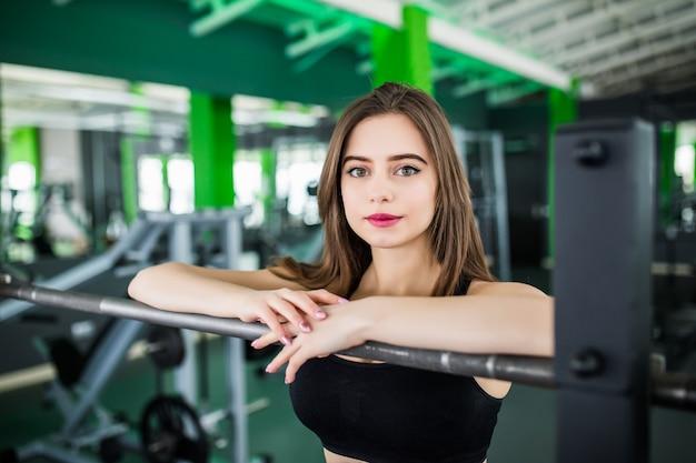 Dame met lang donkerbruin haar en grote ogen poseren in modern fitnesscentrum in de buurt van de spiegel in korte sportkleding