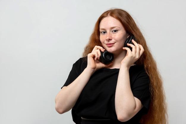 Dame met lang rood haar in zwarte jurk op grijs