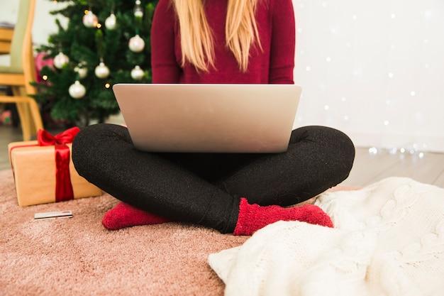 Dame met laptop in de buurt van plastic kaart, geschenkdoos en kerstboom