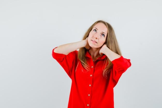 Dame met nekpijn in rood shirt en ziet er moe uit,