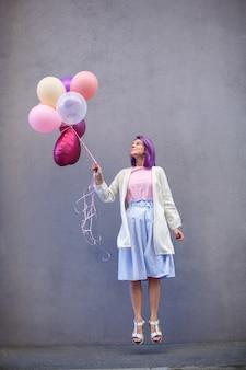 Dame met paars haar dat met ballons in haar hand springt